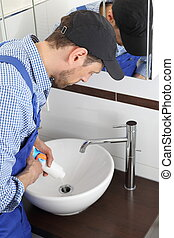 Man pouring a Pipe cleaner in drain pipe - A Man pouring a...