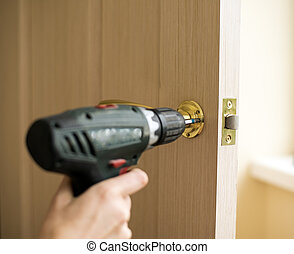 Installation of door lock using a screwdriver to. Carpenter...