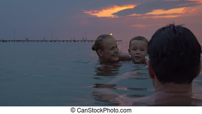 Happy family bathing in the dusk - Cheerful parents and...