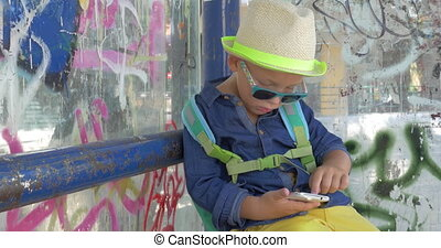 Boy with smartphone at grungy city bus stop - Kid with...