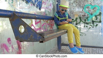 Child using smart phone on grungy bus stop - Boy with...
