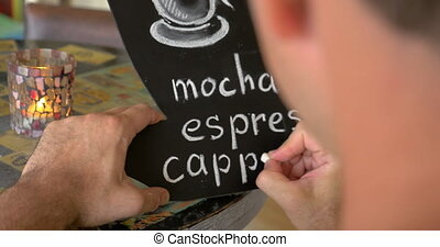 Man writing coffee types on the chalk board - Close-up shot...
