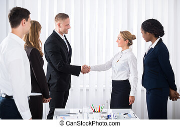 Business Partners Shaking Hands - Businesspeople Looking At...