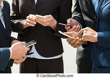 Businesspeople Hands With Mobile Phones - Close-up Of...