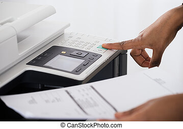 Businesswoman Operating Printer In Office - Close-up Of...