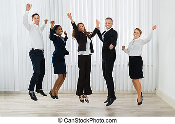 Businesspeople Jumping In Joy - Group Of Professional...