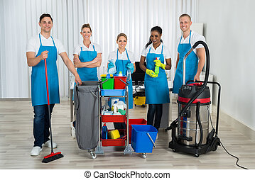 Cleaners With Cleaning Equipments In Office - Group Of Happy...