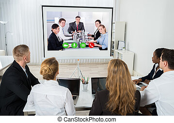 Businesspeople Videoconferencing At Workplace - Group Of...