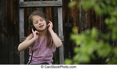 Cute girlie enjoys music with headphones on sitting in the...