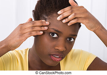 Woman Looking At Pimple On Forehead - Close-up Of Young...
