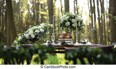 Beautiful wedding decorated table setted for two on nature in the forest. Wedding decoration of white roses bouquets and vintage candelabrum near the chocolate cake
