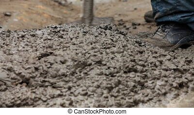 Construction Workers Mixing Concrete - Several construction...