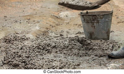 Worker Putting Concrete Into Bucket - CLOSE UP Two frames...