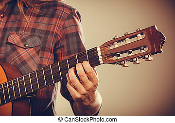 Musicans arm holding strings Guitar with part of guitarist...