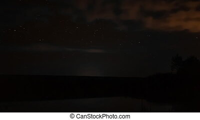 timelapse video of rotating stars in the night sky over...