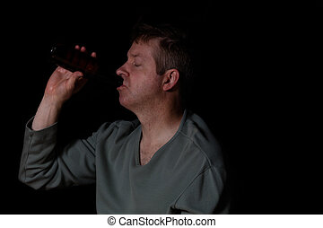 Depressed grungy mature man drinking a beer in dark...