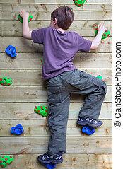 Boy on a climbing wall - Young boy climbing a garden rock...