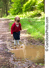 Little Splash - Toddler splashing in a muddy puddle with his...