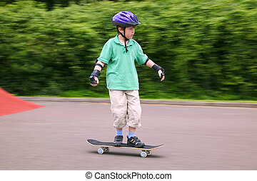 Young boy riding a skateboard - Young 7 year old boy in...