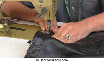 Man sewing leather jacket zipper - Close up of hands of man...