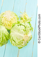 Green cabbage on blue wooden background