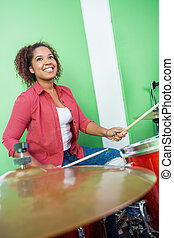 Female Drummer Looking Up While Performing