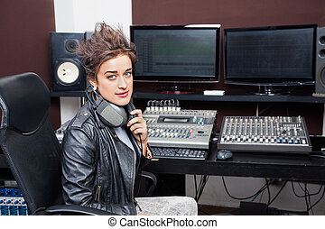 Confident Young Woman Sitting At Mixing Desk - Portrait of...