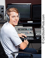 Smiling Young Man Mixing Audio In Recording Studio