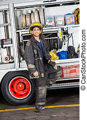 Confident Fireman Standing By Truck At Station - Full length...
