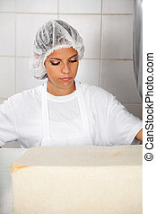 Female Baker Looking At Fresh Bread - Young female baker...