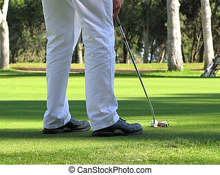 Putting in white trousers - Close up of a golfer lining up a...
