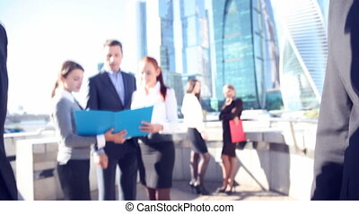 Business people shaking hands outdoors at skyscrapers...
