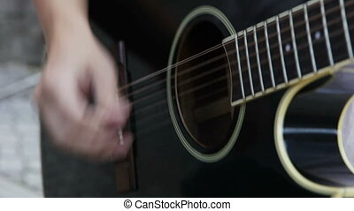 Playing on acoustic guitar A street musician plays the...