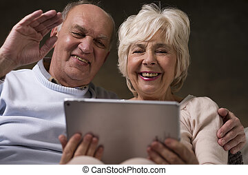 Watching movies online - Smiling happy married older couple...