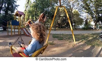 Children ride on a swing at the site - Sister and brother in...