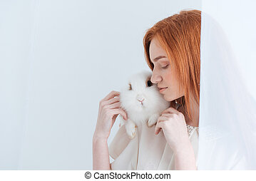 Redhead woman posing with rabbit isolated on a white...