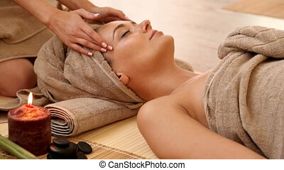 Woman getting facial massage in spa