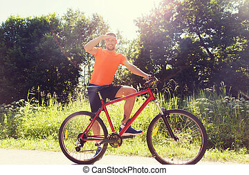 happy young man riding bicycle outdoors - fitness, sport,...