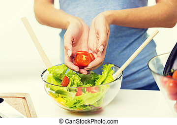 close up of woman cooking vegetable salad at home - healthy...