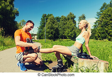 happy couple with rollerskates outdoors - fitness, sport,...