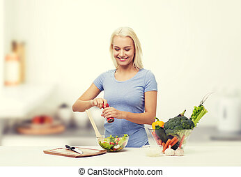 smiling woman cooking vegetable salad on kitchen - healthy...