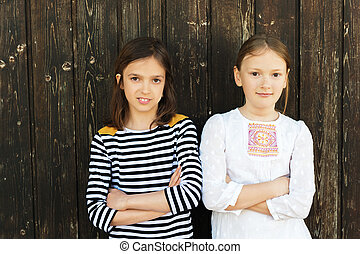 Outdoor fashion portrait of two cute girls of 7-8 years old,...