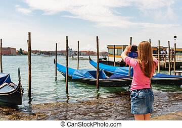 Little girl photographing gondolas in Venice with her mobile...