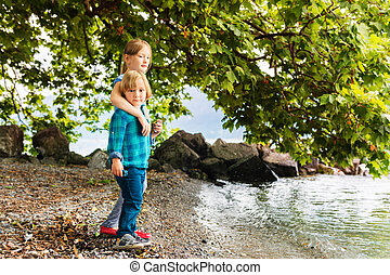 Two cute kids playing outdoors by the lake, big sister...