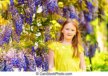 Outdoor stylish portrait of a cute little girl of 8-9 years...