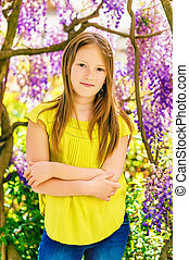 Outdoor stylish vertical portrait of a cute little girl of...