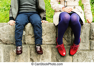 Two pairs of kids feet wearing fashion shoes, little boy...