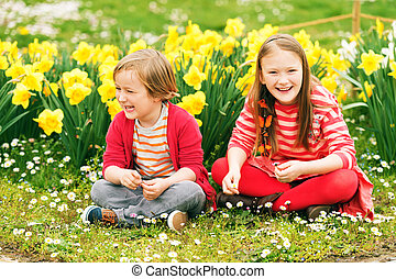 Two cute kids, little boy and his big sister, playing in the...