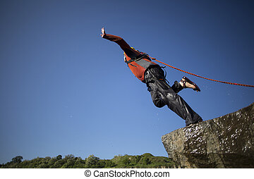 Jump off a cliff with a rope. - A man jumps from a cliff...