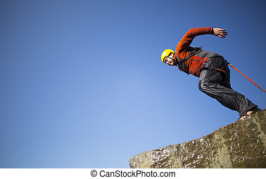 Jump off a cliff with a rope - A man jumps from a cliff into...
